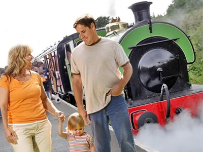 Family day out at a steam railway with steam train in background - based on photo by John Carter